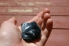 Ein vermutlich bearbeiteter Obsidianstein in Hannahs Hand.